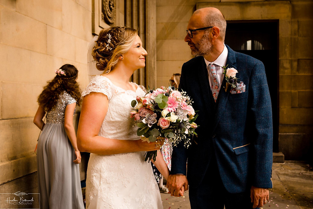 Bride and groom leaving Leeds Town Hall after their wedding in august 2020