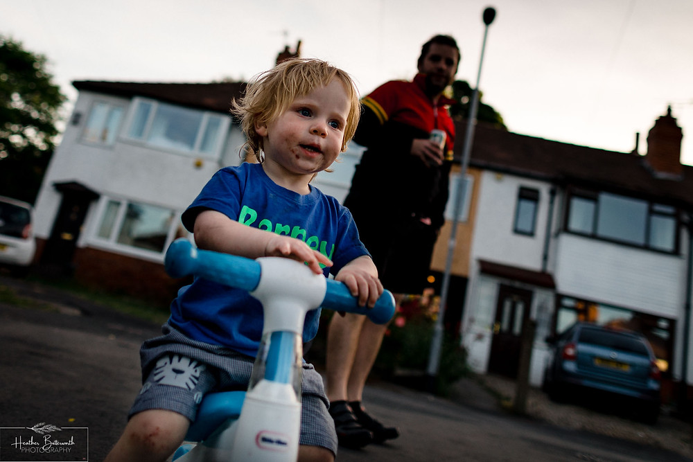 a child on his bike in the street with his dad watching behind