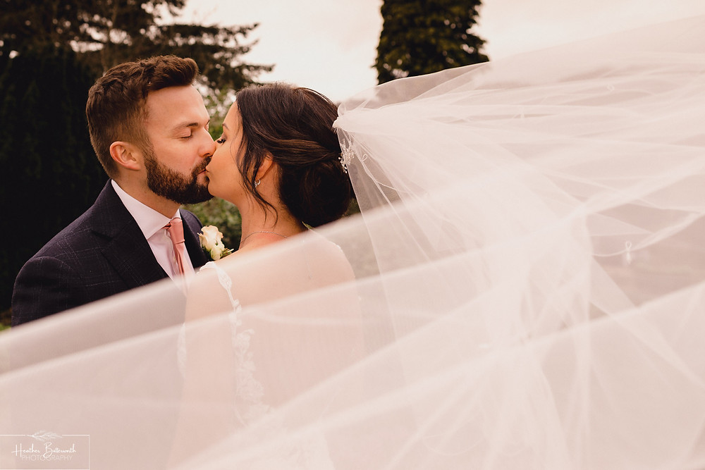 Bride Bex with her new husband Andy in the garden with the veil blowing in the wind at The Burnside Hotel and Spa in Bowness-on-Windermere