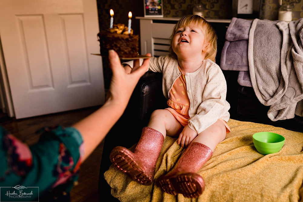 Little girl upset when she wants her birthday chocolate cake straight away but has to be sung to and blow candles out first
