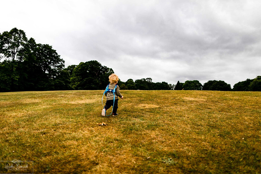 toddler running in roundhay park after restrictions were slightly lifted after the COVID-19 lockdown in Leeds , Yorkshire in June 2020
