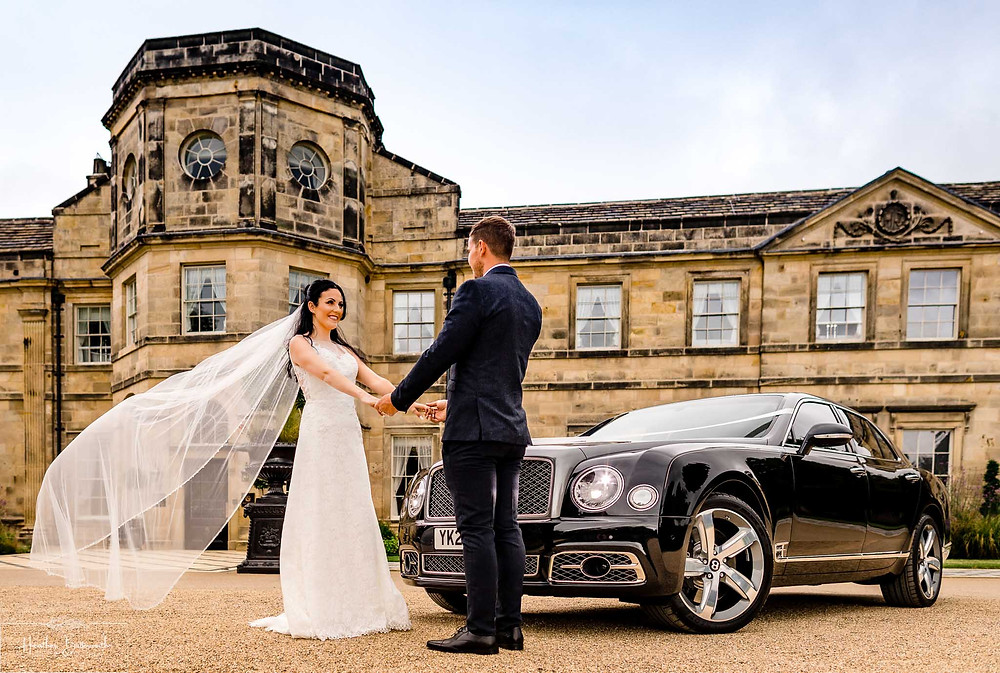 Bride and groom stood next to a Bentley Mulsanne car outside Grantley Hall, Yorkshire in July 2020