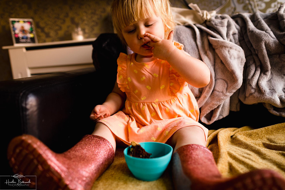 little girl enjoying her chocolate birthday cake at her second birthday party