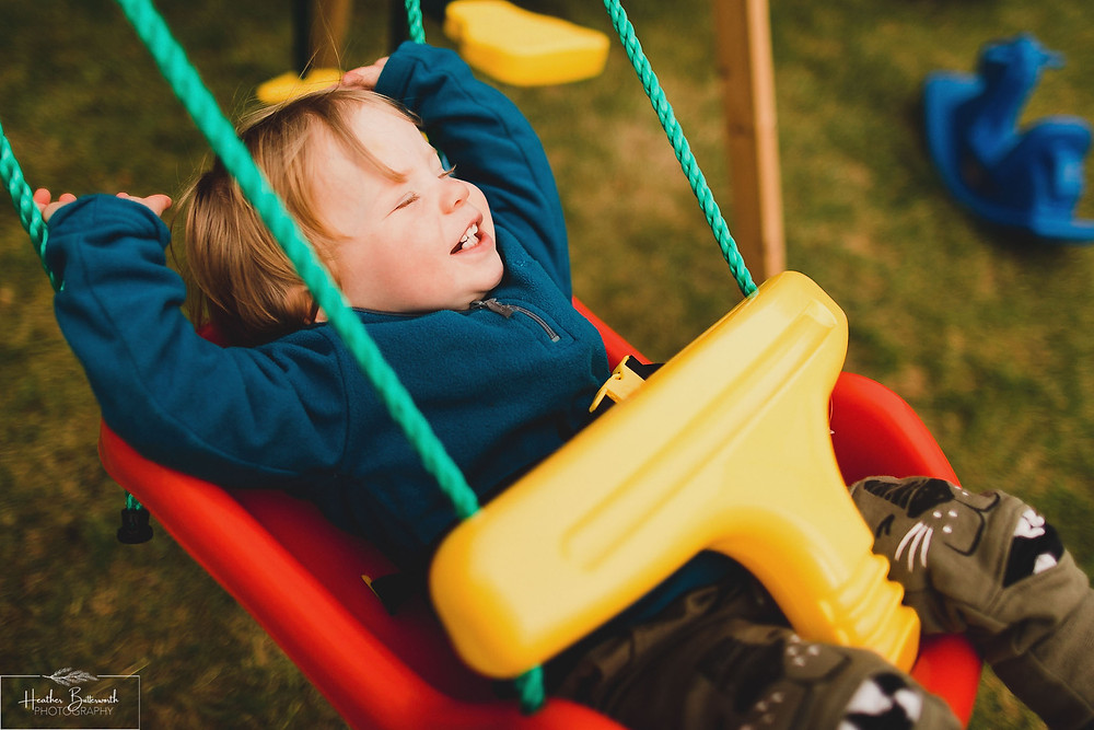 Barney playing on the swing in his family garden in Leeds, Yorkshire. Image by Heather Butterworth Photography