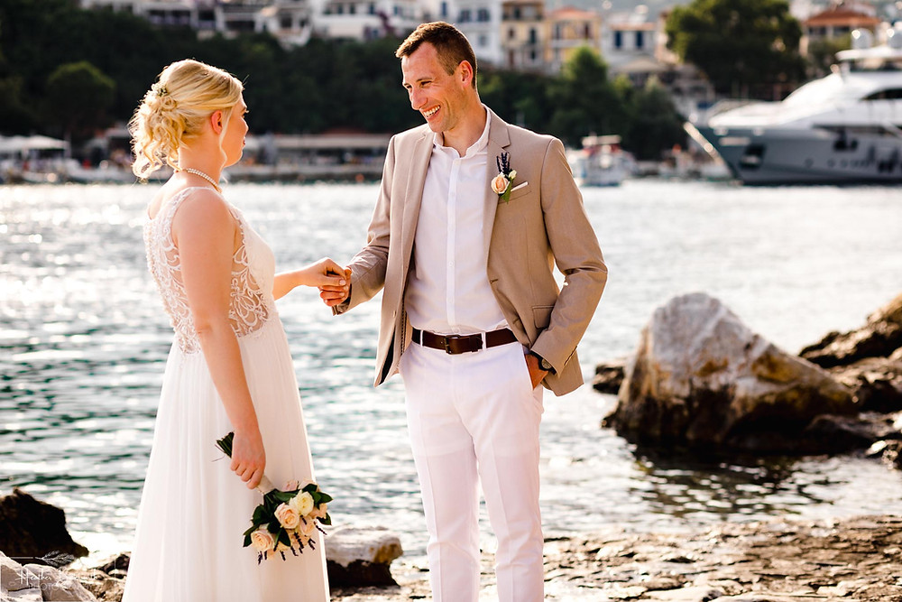 bride and groom stood on the beach in Skiathos town after their wedding at The Bourtzi in Skiathos Town