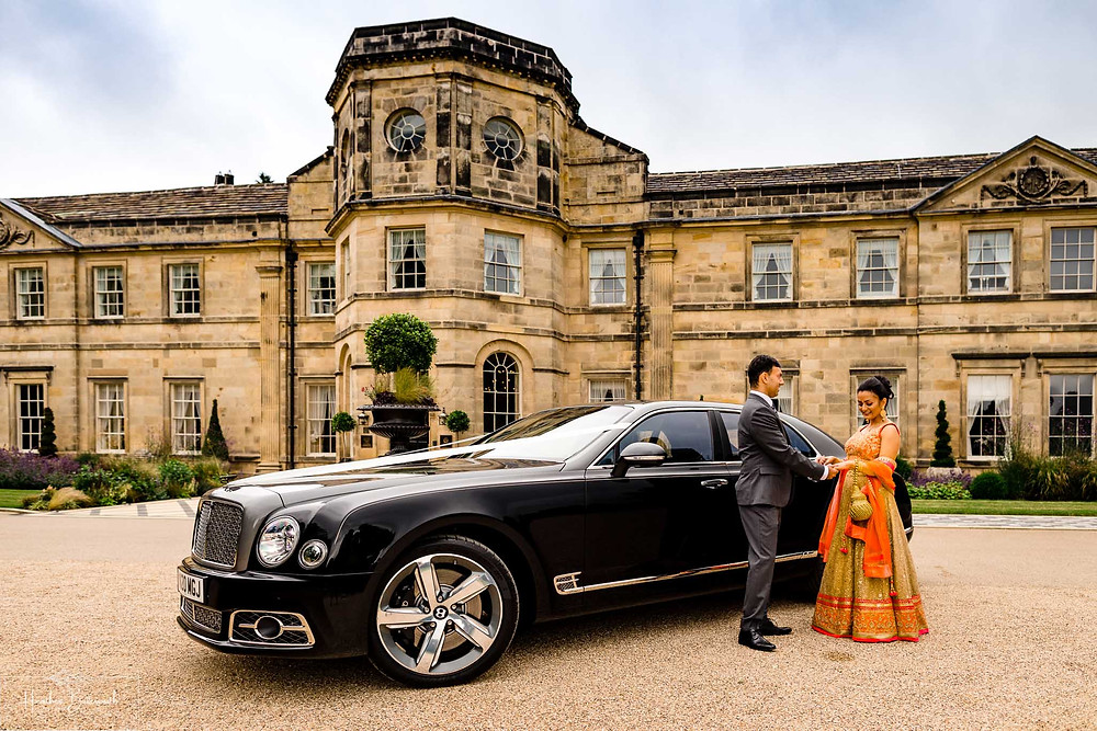 A bride and groom with their Bentley Mulsanne car outside Grantley Hall, Yorkshire in July 2020
