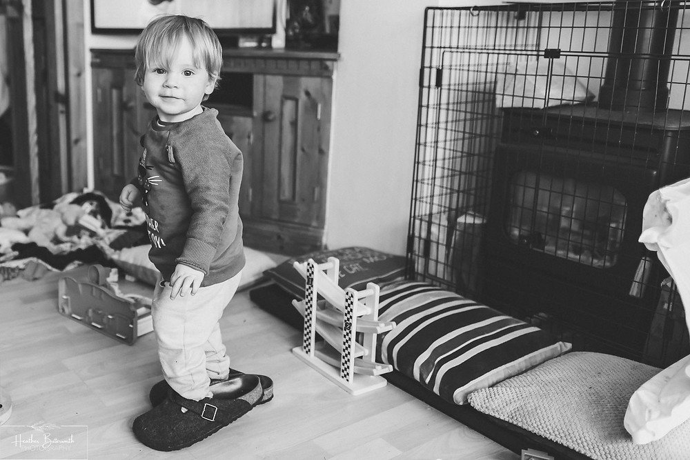 a toddler in from of a log burner wearing his mums Birkenstock slippers