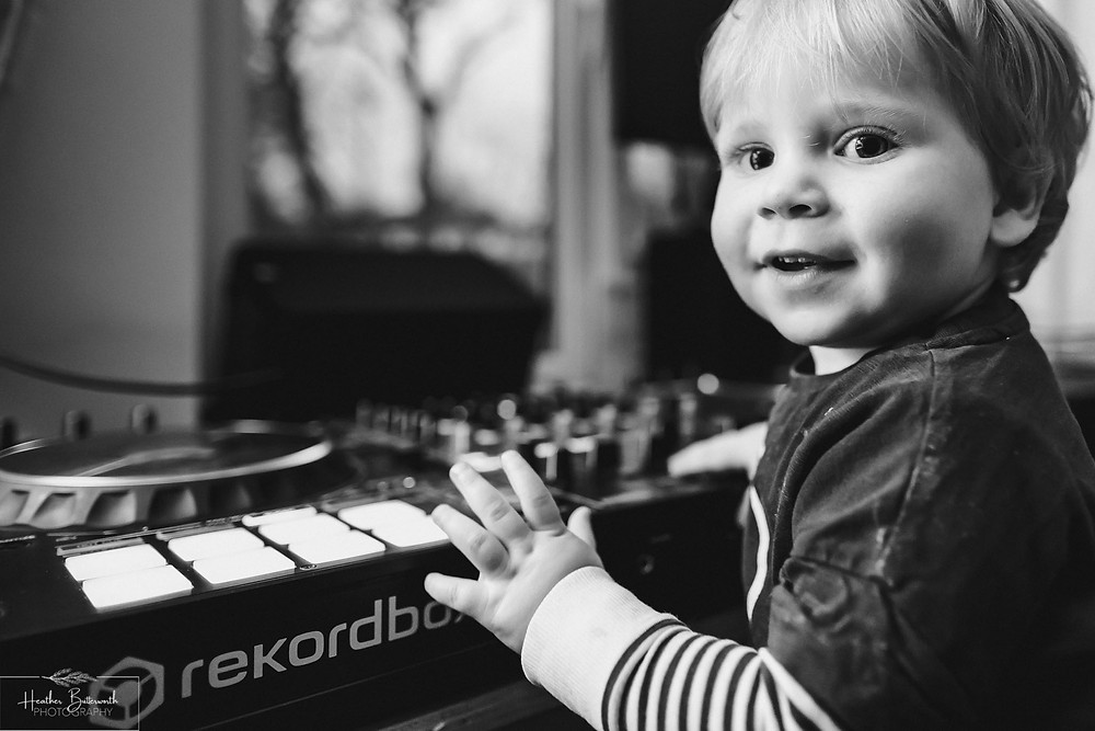 black and white image of a toddler happily playing with DJ equipment