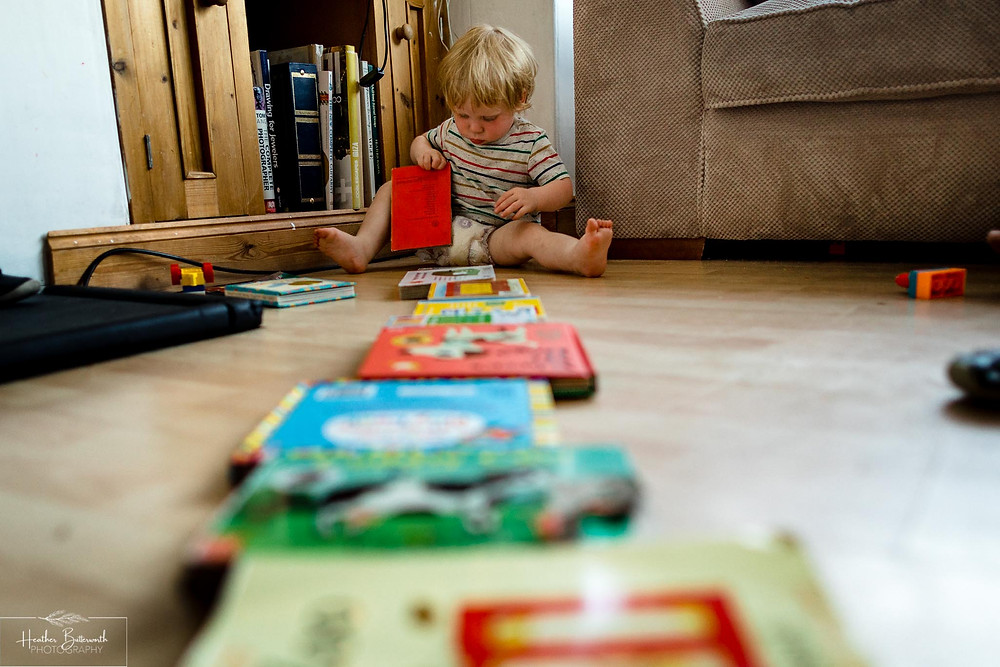 toddler lining up his books in the living room