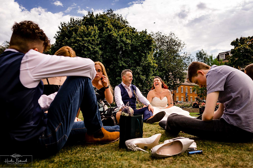 bride and groom laughing with their family as they sit on the grass in Park Square after their wedding at leeds town hall in august 2020
