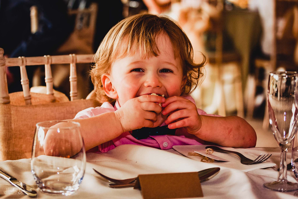 A toddler happy with his food after the wedding ceremony at Moorlands Inn, Halifax, Yorkshire