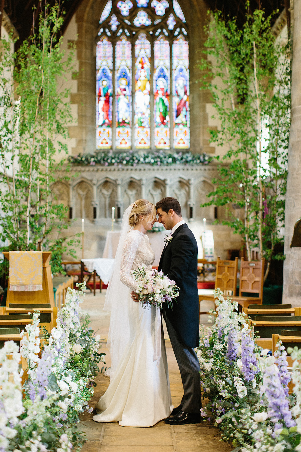 Bride and groom in a church surrounded by flowers