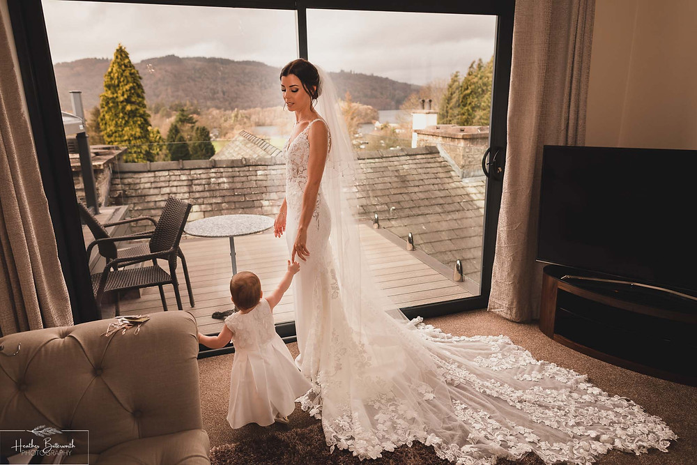 Bride Bex with her baby daughter stood by a window during bridal preparations at The Burnside Hotel and Spa in Bowness-on-Windermere