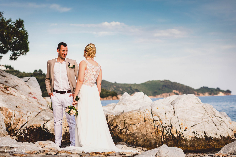groom looking at the bride who has her back to the camera on the beach in skiathos