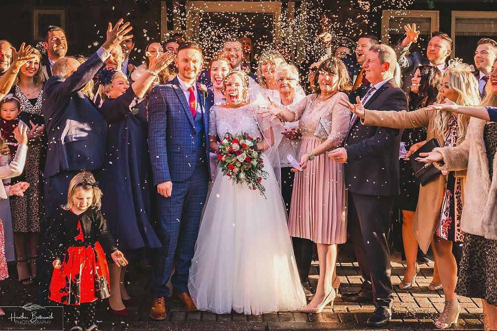 A happy bride and groom having confetti thrown at them after their wedding at The Woodman Inn in Thunderbridge near Leeds, Yorkshire