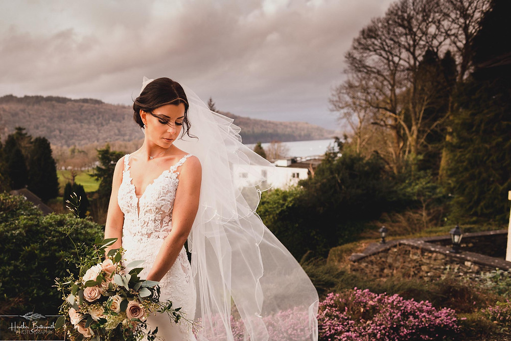 Bride Bex in the garden after their ceremony with her hair and veil blowing in the wind at The Burnside Hotel and Spa in Bowness-on-Windermere