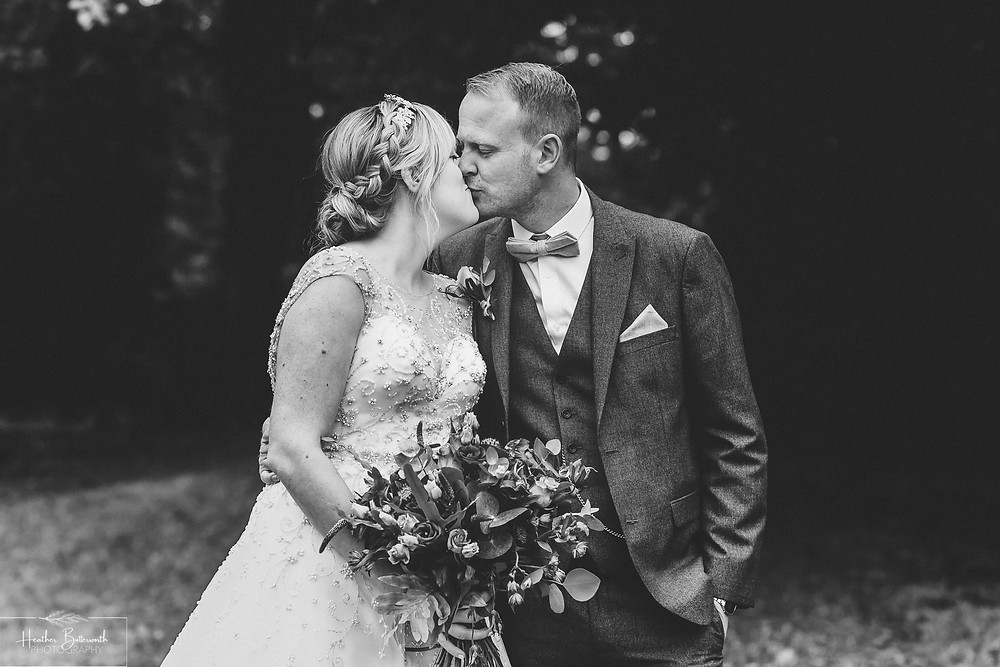 Bride and Groom kissing in the grounds after their wedding at Adel Parish Church in Leeds, Yorkshire