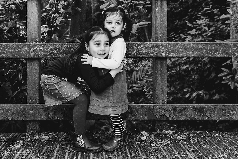 black and white image of two young sisters hugging with a toddler grabbing her sister in a wood.