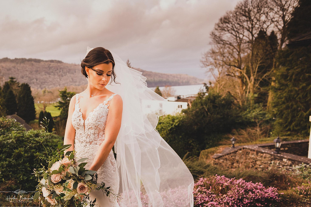 bride looking down whilst her veil blows in the wind with lake windermere behind them