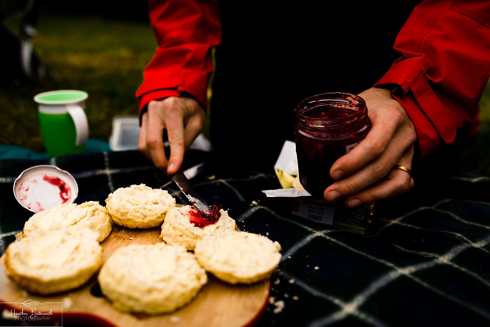 scones at a picnic with jam spread on them