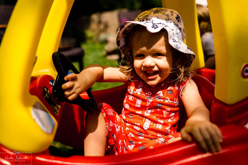 girl playing in a red and yellow toy car