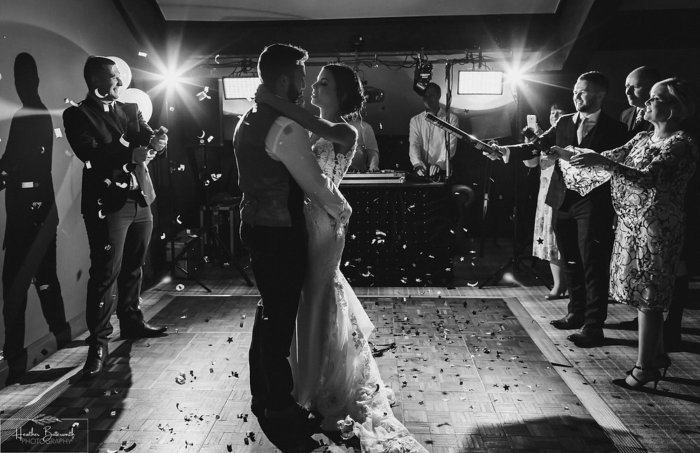 Bride Bex and Groom Andy dancing with confetti cannons in monochrome at their evening reception at The Burnside Hotel and Spa in Bowness-on-Windermere