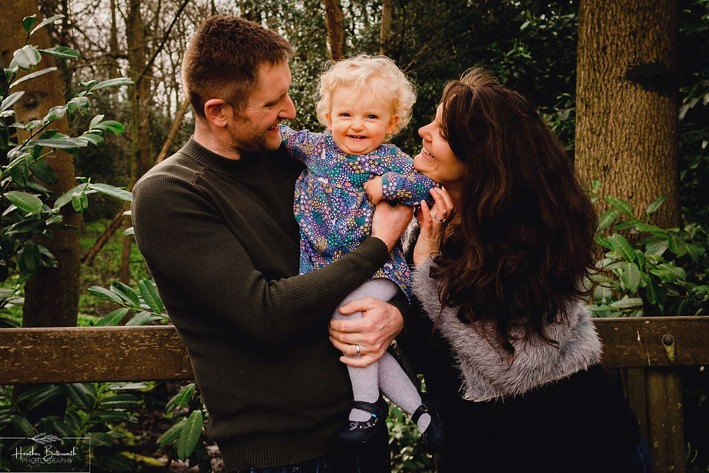 parents stood with their toddler daughter looking at the camera in a wood with trees behind them in roundhay park