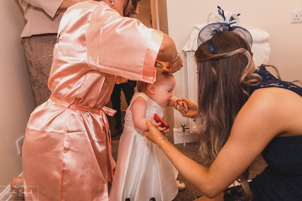 The brides baby daughter having her hair done by fellow bridesmaids during bridal preparations at The Burnside Hotel and Spa in Bowness-on-Windermere