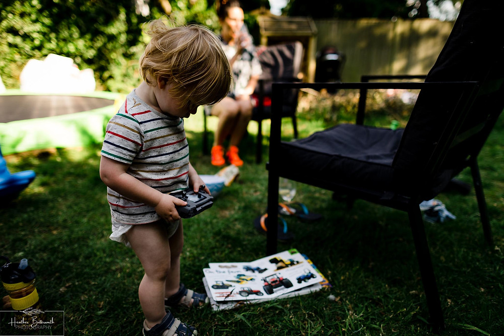 a toddler happily playing with a remote control in the garden