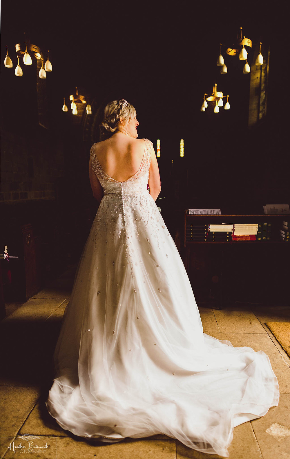 Bride in natural light in the church after her wedding at Adel Parish Church in Leeds, Yorkshire