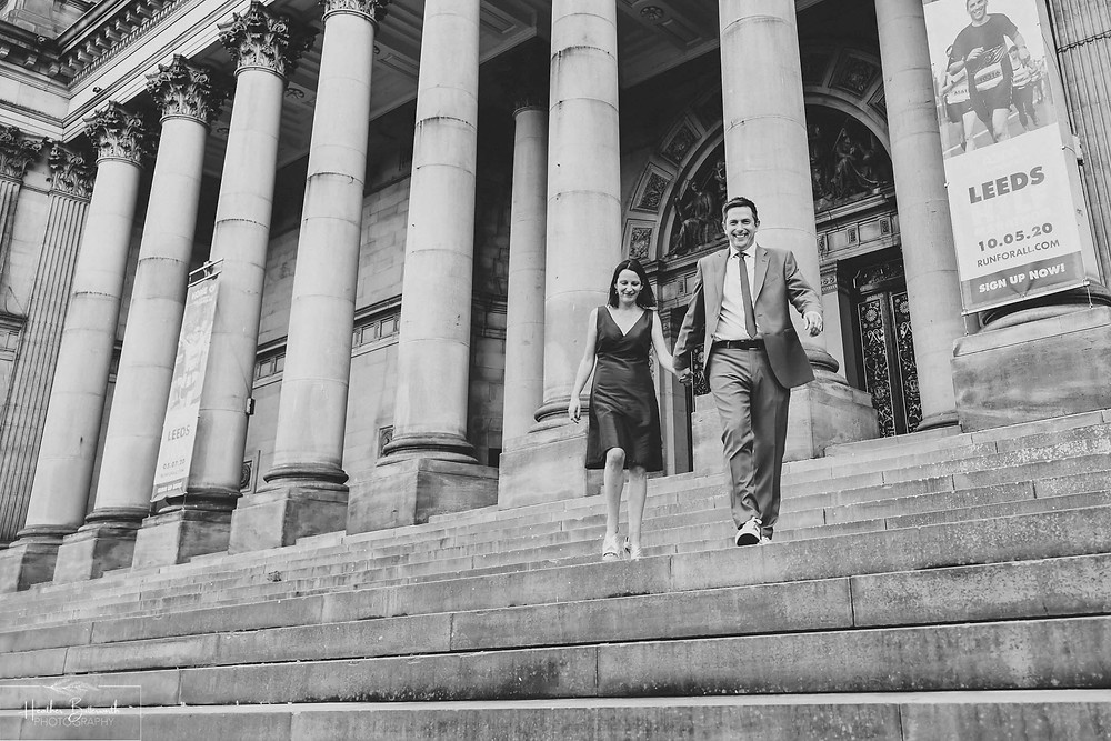 Bride and groom walking down the steps after their wedding ceremony at Leeds Town Hall, Yorkshire