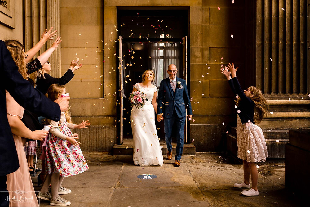 Bride and groom leaving Leeds Town Hall while guests throw confetti after their wedding in august 2020