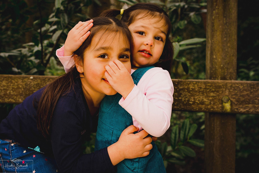 two young sisters hugging with a toddler grabbing her sisters nose in a wood.