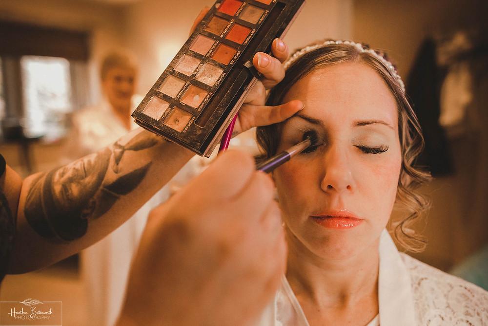 Bride having her make up done before her wedding at The Woodman Inn in Thunderbridge near Leeds, Yorkshire
