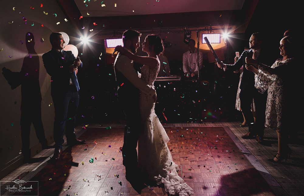Bride Bex and Groom Andy dancing with confetti cannons at their evening reception at The Burnside Hotel and Spa in Bowness-on-Windermere