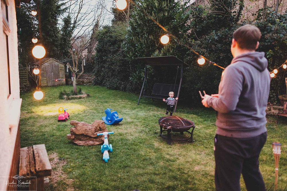 a toddler laughing with hands held up also looking surprised and excitedly at his dad who is flying a drone in the garden