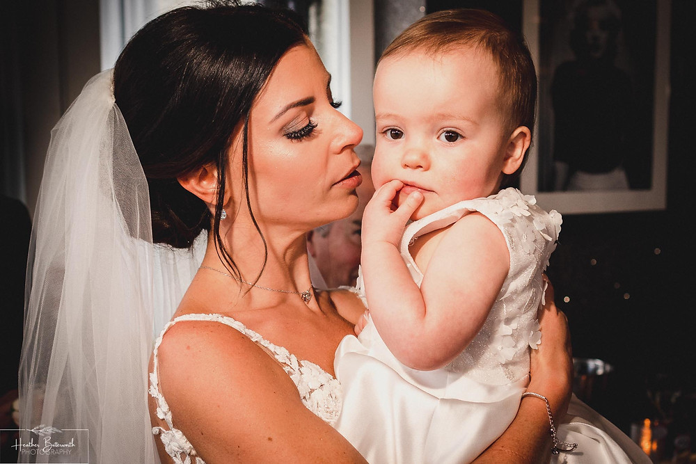 Bride hugging her baby daughter at The Burnside Hotel and Spa in Bowness-on-Windermere
