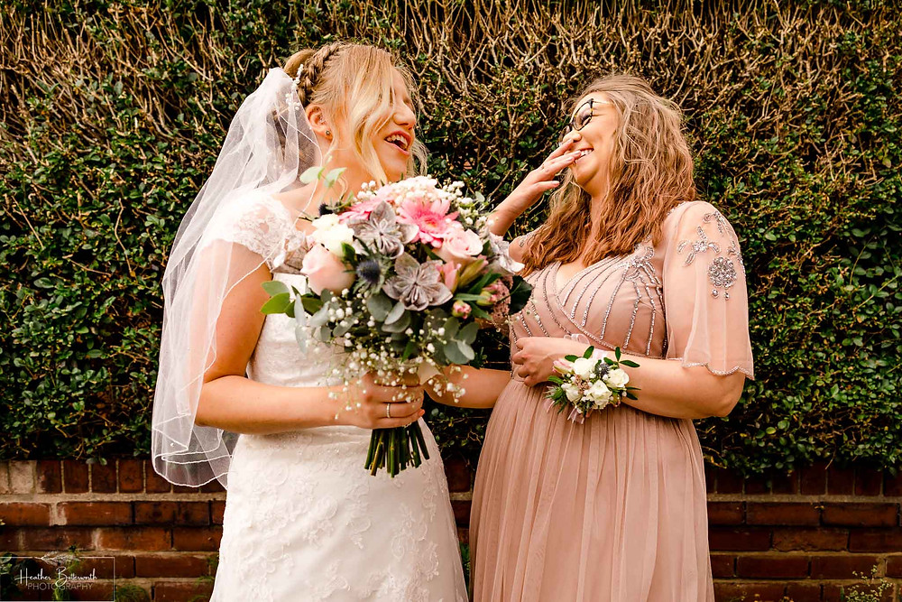 bride stood laughing with her sister and bridesmaid outside her house before her wedding in Leeds Yorkshire UK in august 2020