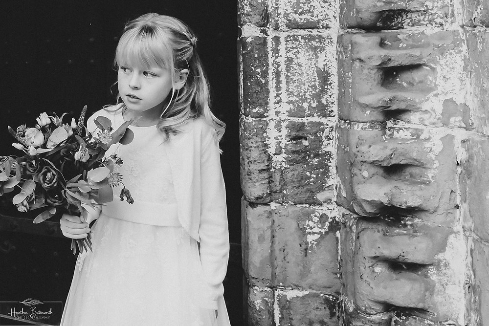 Bridesmaid waiting for the bride at before the wedding at Adel Parish Church in Leeds, Yorkshire