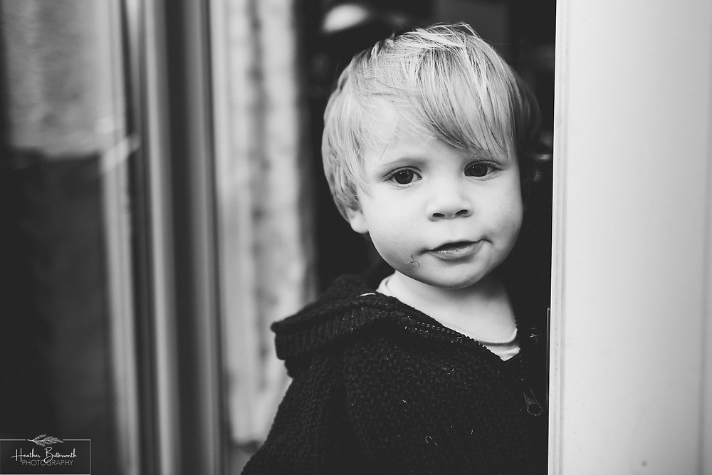 black and white image of a toddler looking at the camera from a doorway