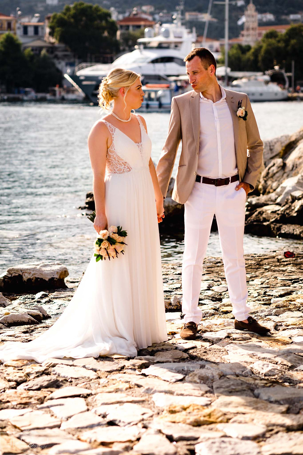 bride and groom holding hands on the beech in skiathos in June 2019