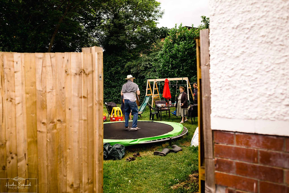 man jumping on a trampoline in a garden in july 2020