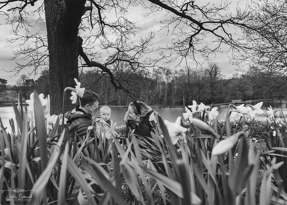 black and white image of parents sat on a rug with their toddler son in roundhay park