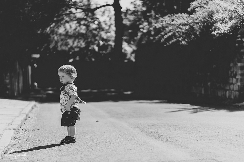 black and white image of a toddler in the street