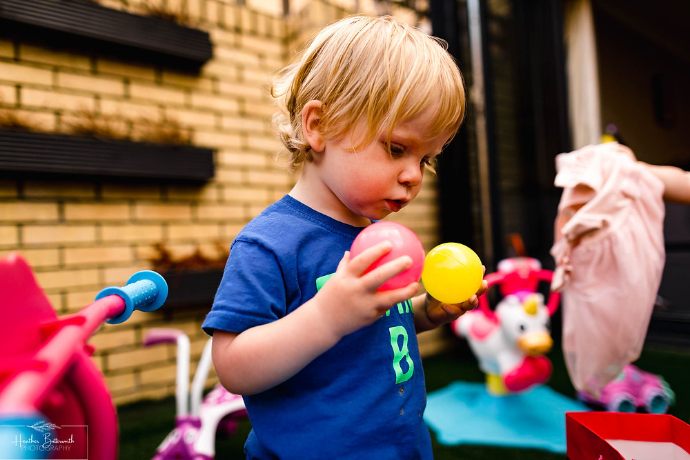 little boy playing in a garden with small plastic balls from a ball pool