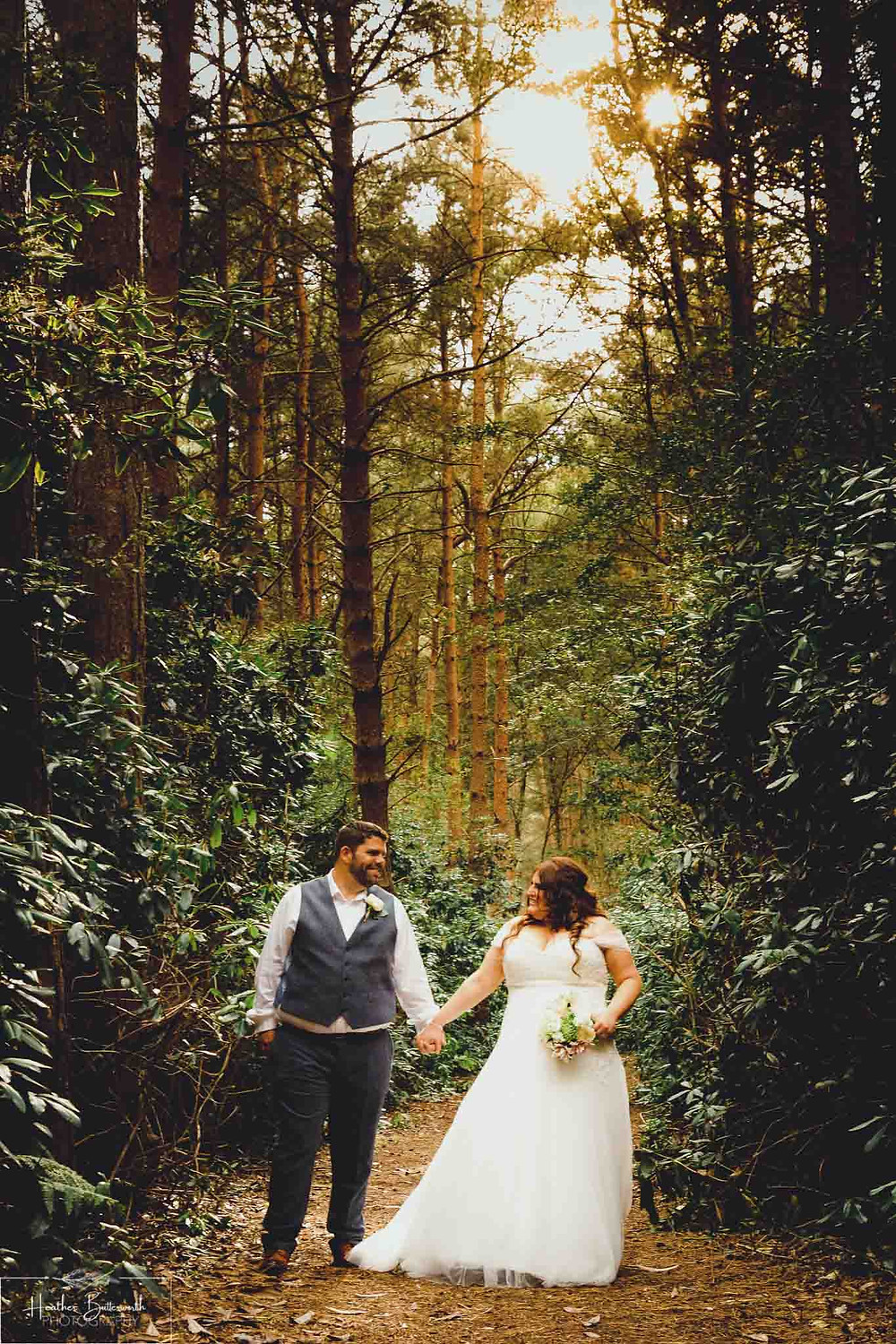 Bride and groom holding hands and gazing at each other in the woods with the sun behind them at Sandburn Hall in York, Yorkshire