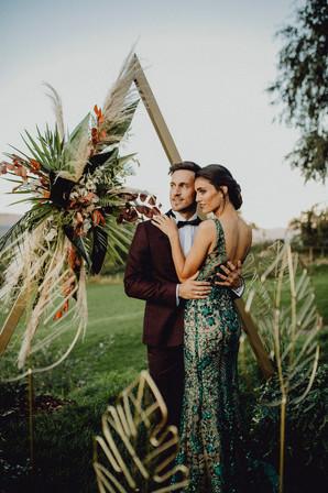 elegantes Brautpaar vor einem dreieckigen Trauungsbogen, Trauungsbogen mit Bohoblumenschmuck, Hochzeit Fernblick, Ivory Rose Photography