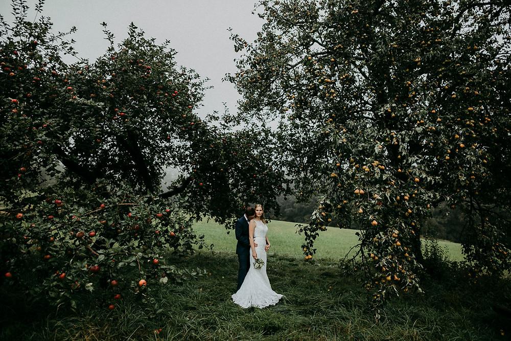 Brautpaar im Apfelhain bei Regen