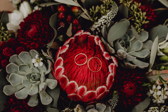 Detailfoto Eheringe, bordeauxfarbener Brautstrauß, Sukkulente Hochzeitsdekoration