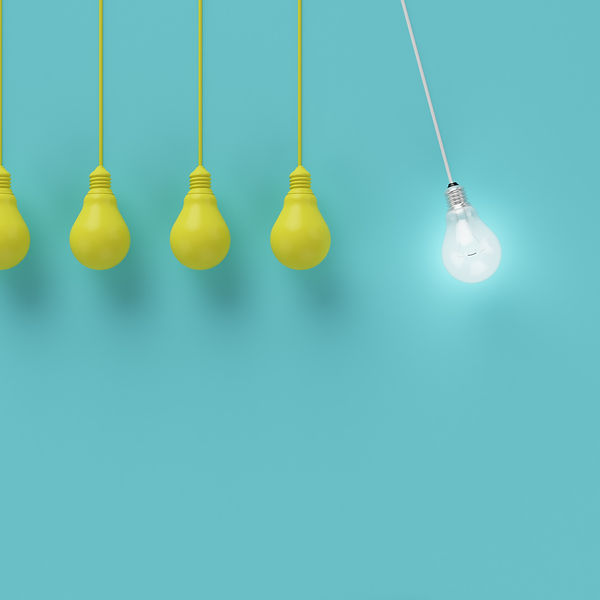Hanging yellow light bulbs with glowing one different idea on light blue background , Minimal concep